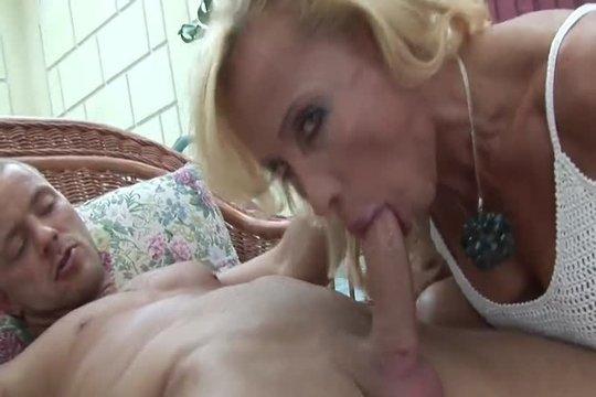 Зрелая блондинка сосет у молодого парня и кокетливо смотрит в камеру