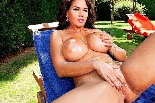 Брюнетка с большой грудью мастурбирует пизду у себя во дворе на лежаке