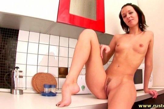 Молодая русская телка небрежно ласкает бритую пизду на кухне, желая заняться сексом